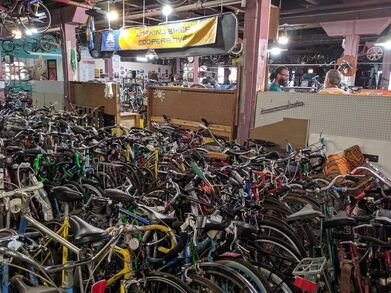 Room full of donated bikes pressed closely together