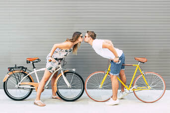 Two cyclists standing over a bike leaning in and kissing